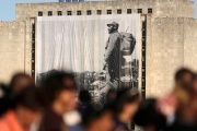 A large portrait of Cuba's late President Fidel Castro hangs from a building while people wait in line to pay tribute to Castro in Havana, Cuba, Nov. 28, 2016.