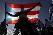 A protester holding Puerto Rico's flag takes part in a march to improve health care benefits in San Juan, Puerto Rico