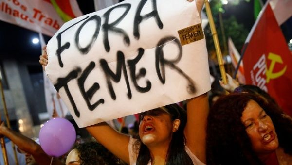 "A woman holds a banner that reads ""Temer Out."""