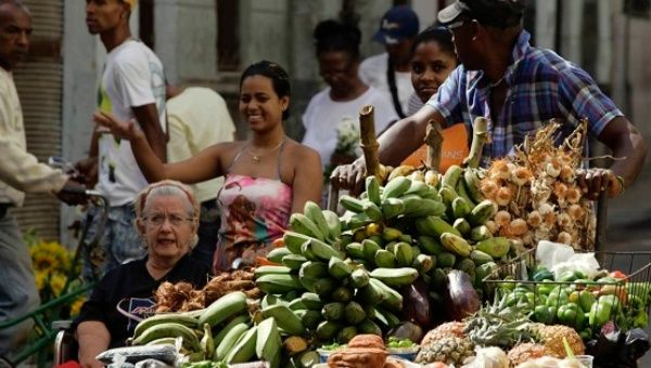 A man pushes his cart with vegetables and fruit for sale on a street in Havana, Cuba, March 14, 2012.