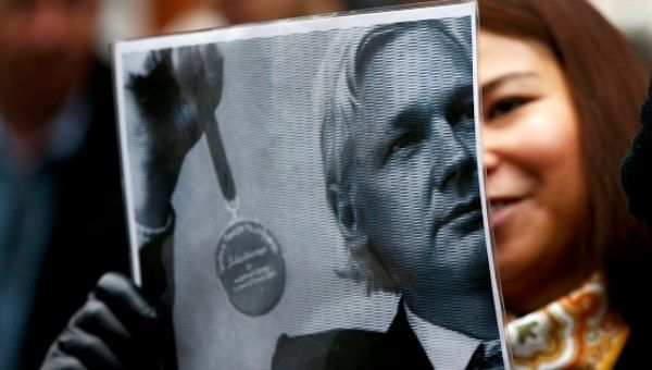 A supporter of Julian Assange holds a poster after a prosecutor from Sweden arrived at Ecuador