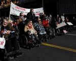 Demonstrators with physical disabilities take part in a protest calling on the government not to cut down their monthly disability subsidy and pension, in Athens, Greece, Dec. 2, 2016.