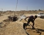 A worker shovels sand outside a tunnel on the border between Egypt and the southern Gaza Strip, Oct. 8, 2013.