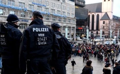 Police look on as refugees demonstrate against violence near the main Cologne train station.