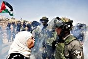 A Palestinian woman argues with an Israeli border policeman during a protest against Jewish settlements in the West Bank village of Nabi Saleh, near Ramallah