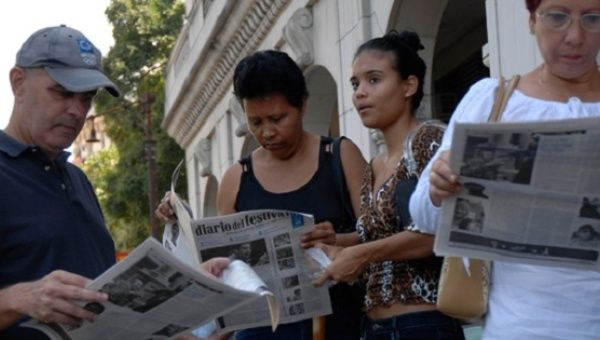 People read the Festival newspaper outside the Payret movie theater in Havana, Cuba, Dec. 6, 2008.