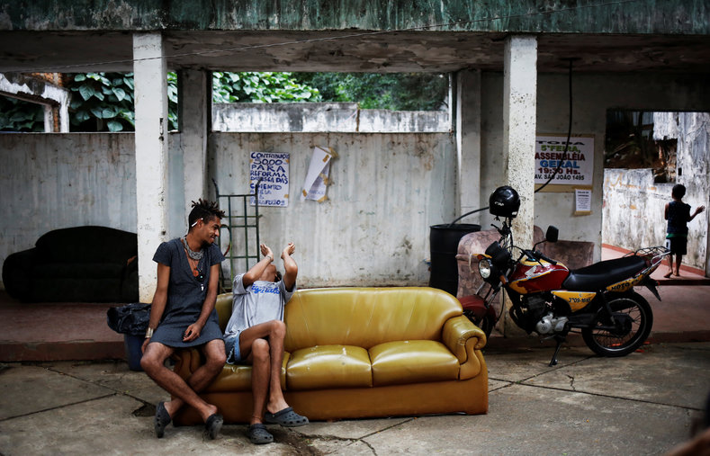 Teflon (L), 19, and Gaby, 18, sit on a sofa outside the occupied building.