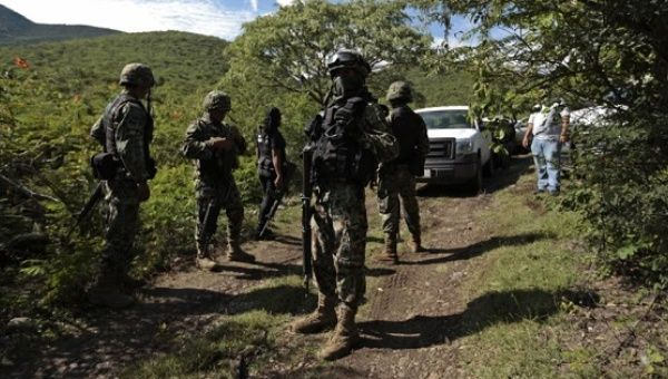 This file photo show Mexican soldiers guarding an area where a mass grave was found, in Colonia las Parotas on the outskirts of Iguala, in Guerrero, Mexico.