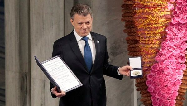 Nobel Peace Prize laureate Colombian President Juan Manuel Santos poses with the medal and diploma during the Peace Prize awarding ceremony at the City Hall in Oslo, Norway December 10, 2016.