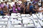 Family members of victims of the El Mozote massacre present the remains of some of the victims in white coffins, commemorating 35 years since the bloody event.