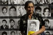 Apolonia Escamilla holds a portrait of a family member at the Monument to Memory and Truth in San Salvador, Jan. 15, 2013.