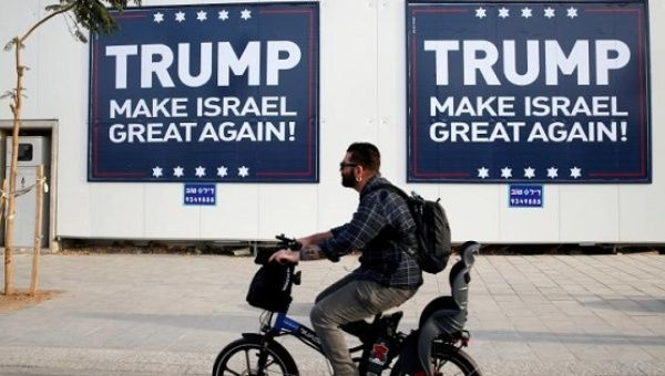 People walk past signs bearing the name of U.S. President-elect Republican Donald Trump in Tel Aviv, Israel Nov. 14, 2016.