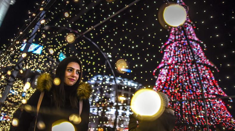 La plaza central de Skopie en Macedonia es alumbrada por un árbol navideño. Una mujer pasea debajo de un túnel iluminado.