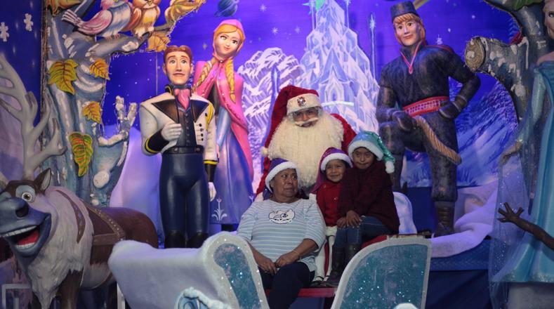 La figura de Papá Noel o San Nicolás es universal, una familia posa en el carruaje de Papá Noel como parte de las tradiciones y festejos navideños en Ciudad de México.