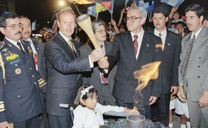 Guatemalan President Alvero Arzu (C) lights a peace torch with Guatemalan National Revolutionary Unity (URNG) commander Rolando Moran (2nd R) at the Plaza de la Constitución in Guatemala City, as a girl, victim of the war, looks on, Dec. 29, 1996.