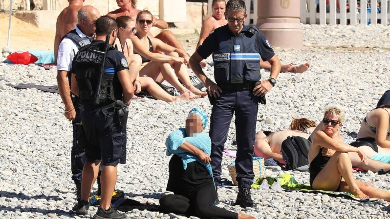 In France, Islamophobia is taking unprecedented proportions: in this photo that went viral, armed French police confront a woman on a beach and make her remove some of her clothing as part of a controversial ban on the burkini.
