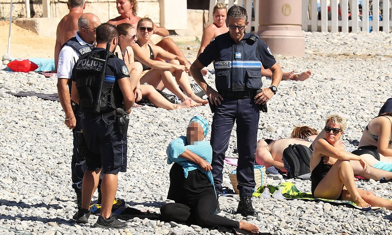 In this photo that went viral, armed French police confront a woman on a beach and make her remove some of her clothing as part of a controversial ban on the burkini.