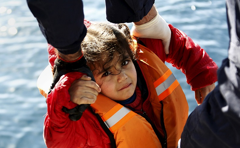Rescuers help a girl out of a dinghy carrying refugees and migrants onto a Greek coast guard vessel in the open sea between Turkey and Lesbos. The refugee crisis in Europe is above all a humanitarian crisis of people fleeing conflict zones.