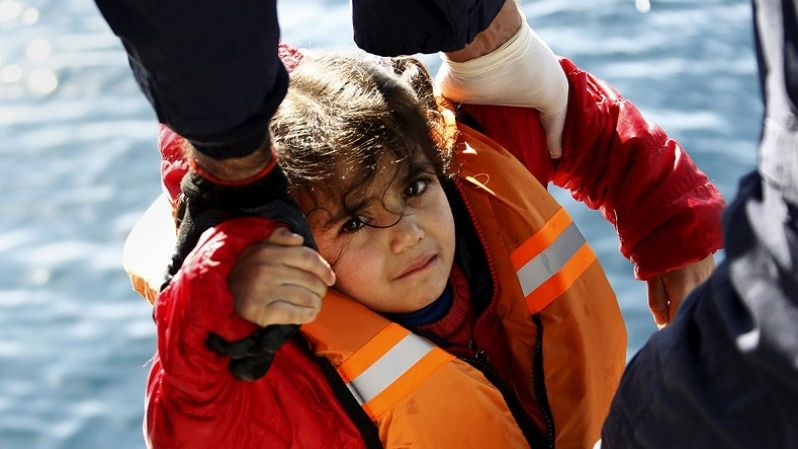 Rescuers help a girl out of a dinghy carrying refugees and migrants onto a Greek coast guard vessel in the open sea between Turkey and Lesbos. The refugee crisis in Europe is above all a humanitarian crisis of people fleeing conflict zones, Feb. 8, 2016.