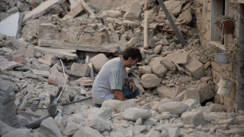 A man reacts to his damaged home after a strong earthquake hit Amatrice on August 24. Italy