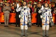 Chinese astronauts Jing Haipeng (R), Chen Dong wave before the launch of Shenzhou-11 manned spacecraft, in Jiuquan, China, Oct. 17, 2016