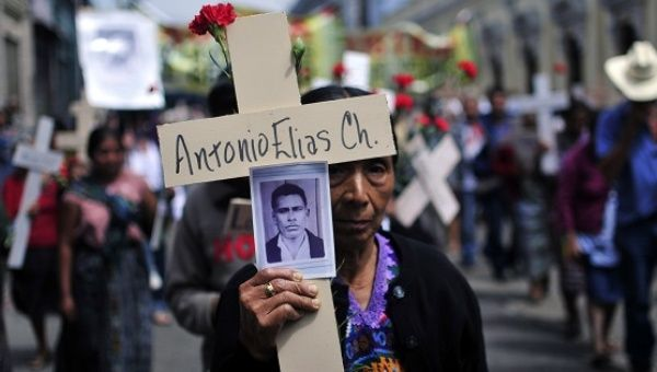 A Mayan woman carries a photo of her husband, who was disappeared by the Guatemalan army in 1982, during an event in Guatemala City, Feb. 25, 2010.