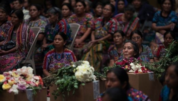 Kakchiquel Mayan women listen to instructions from forensic anthropology experts next to boxes containing the remains of ten wartime victims.