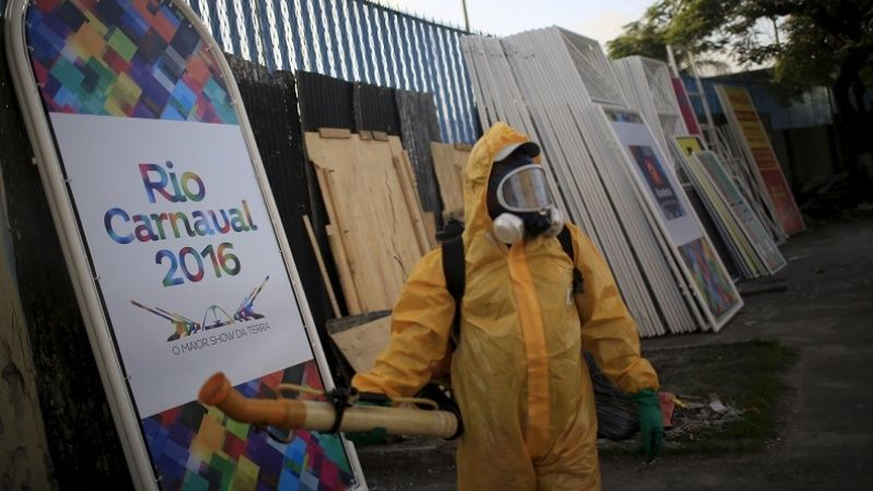 A municipal worker next to a poster promoting Rio Carnival 2016 before fumigating the area with insecticide, Rio de Janeiro, Brazil, January 26, 2016. The International Olympic Committee assured that the teams that will travel to the Rio de Janeiro Olympic Games in August will be safe against the Zika virus.