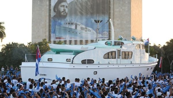 An image of late Cuban President Fidel Castro hangs on a building as a replica of the Granma yacht passes by during a march in Havana, Jan. 2, 2017.