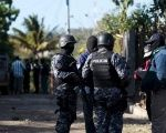 Policemen and investigators gather at a crime scene after a shooting at La fuente neighborhood in the town of Zaragoza, El Salvador, Feb. 8, 2016.