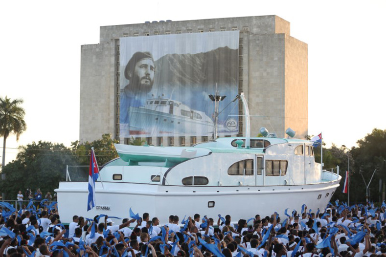 "An image of late Cuban President Fidel Castro hangs on a building as a replica of the Granma yacht passes by during a march to mark the Armed Forces Day and commemorate the landing of the Granma, which brought the Castro brothers, Ernesto ""Che"" Guevara and others from Mexico to Cuba to start the revolution in 1959, in Havana, Cuba, Jan. 2, 2017."