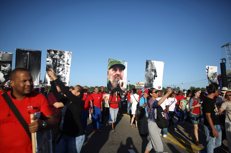 People march with images of Cuba