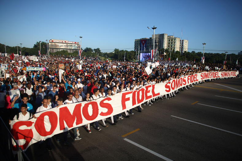 "People march with a banner that reads ""We are all Fidel"" to mark the Armed Forces Day and commemorate the landing of the yacht Granma, which brought the Castro brothers, Ernesto ""Che"" Guevara and others from Mexico to Cuba to start the revolution in 1959, in Havana, Cuba, Jan. 2, 2017."