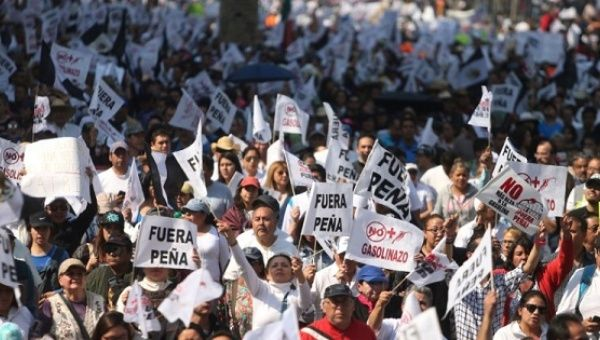 Protesters march during a demonstration against the rising prices of gasoline enforced by the Mexican government at downtown in Mexico City