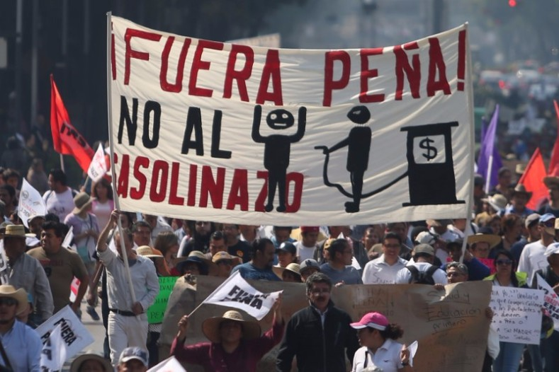 "Protesters march during a demonstration against the rising prices of gasoline enforced by the Mexican government at downtown in Mexico City, Mexico, Jan. 7, 2017. The sin reads, ""Out Pena. No more high prices of gasoline."""