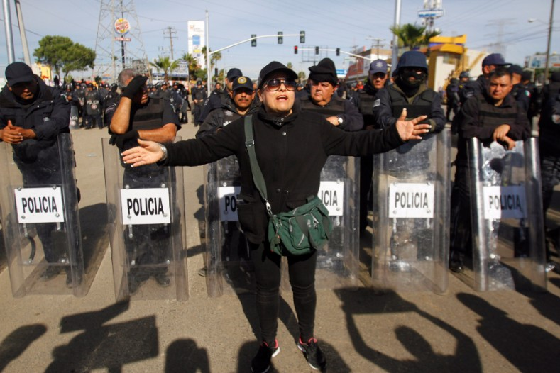 A demonstrator gestures in front of policemen as a group of them blocked the entrance of a Pemex gas storage station during a protest against the rising prices of gasoline enforced by the Mexican government, in Rosarito, Jan. 7, 2017.