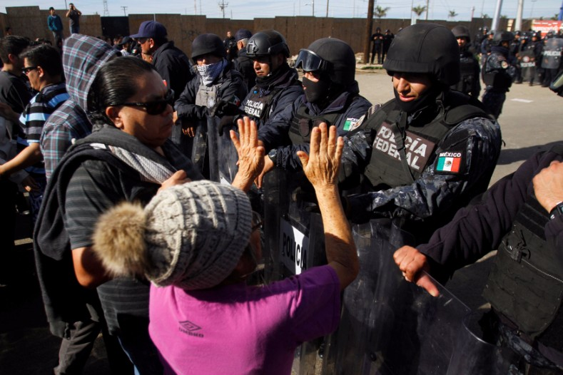 Demonstrators speak with policemen as they block the entrance of a Pemex gas storage station during a protest against the rising prices of gasoline enforced by the Mexican government, in Rosarito.