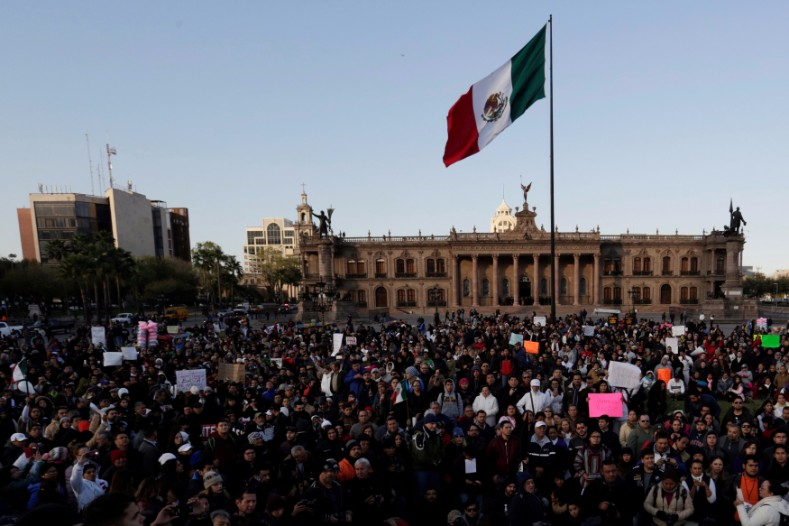 Demonstrators hold up placards during a protest against the rising prices of gasoline enforced by the Mexican government at the Macroplaza in Monterrey.