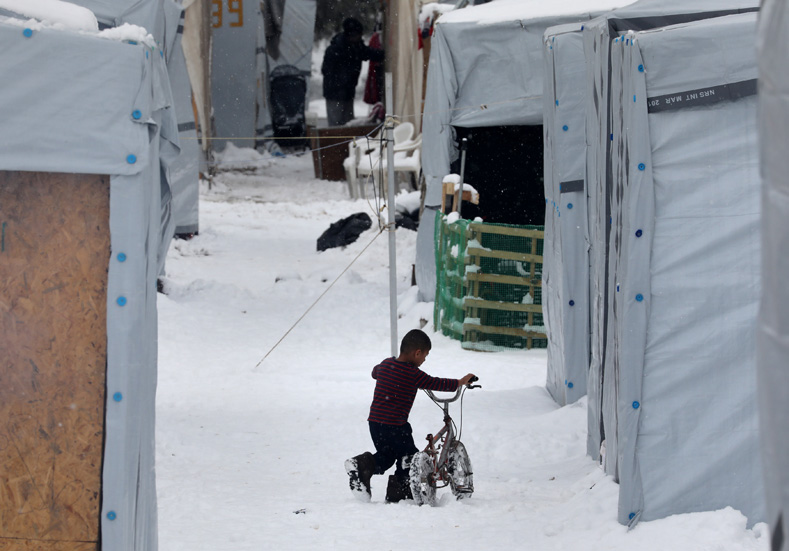 A stranded Syrian refugee child tries to move his bicycle during a snowstorm at a refugee camp north of Athens, Greece, Jan. 10, 2017.