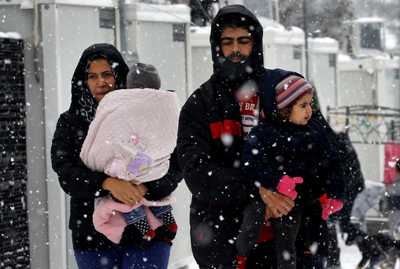 Stranded Syrian refugees carry their children through a snow storm at a refugee camp north of Athens, Greece, Jan. 10, 2017.