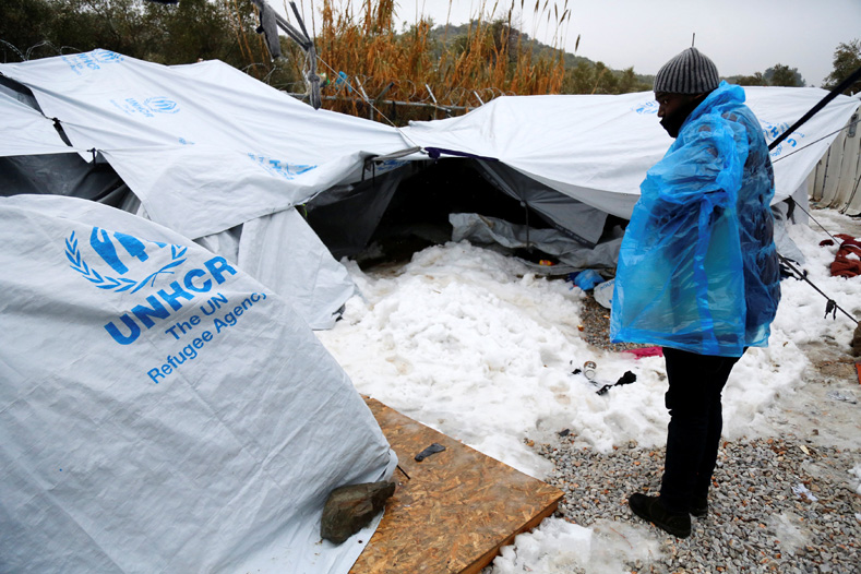 A migrant is covered with a plastic cover to protect from low temperatures as snow lays next to tents provided by the UNHCR at the refugee camp of Moria on the Greek island of Lesbos, January, 10, 2017.