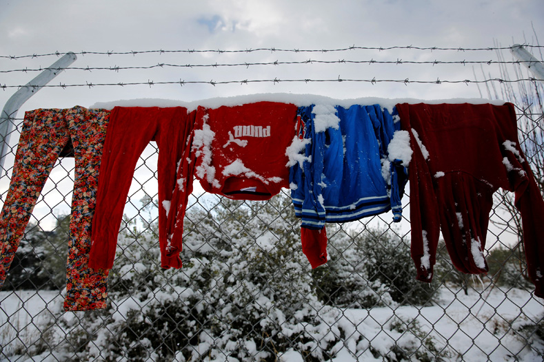 Clothes that belong to stranded refugees are covered with snow as they hang on a fence during a show storm at a refugee camp north of Athens, Greece, Jan. 10, 2017.