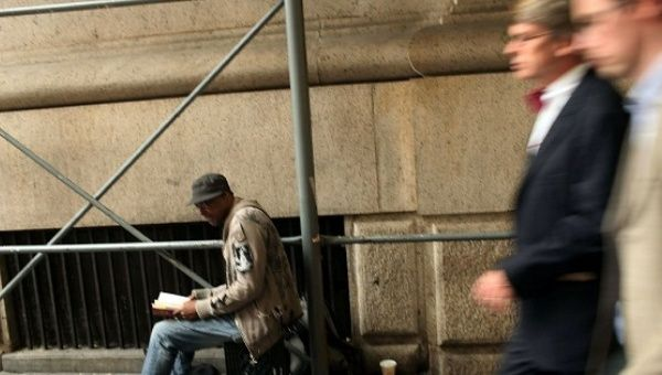 Businessmen walk by a homeless man on a New York street, Sep. 28, 2010.