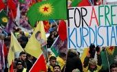 Members of the Kurdish community hold banner and flags during a rally in front of the Gare du Nord railway station in Paris, France, Jan. 7, 2017.