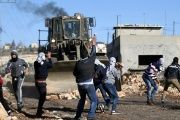 Palestinian protesters throw stones toward Israeli troops during clashes following a protest against the nearby Jewish settlement of Qadomem, in the West Bank.