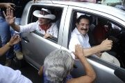 Honduras' former President Manuel Zelaya and his wife Xiomara Castro de Zelaya greet supporters from a car in Tegucigalpa in 2012.