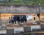 Police patrol the Alcazuz prison, in the Brazilian city of Natal, after a riot left at least 10 inmates dead.