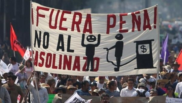 Protesters march during a demonstration in downtown Mexico City against the rising prices of gasoline implemented by the Mexican government.