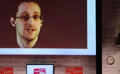Edward Snowden is seen on the screen during a live remote interview at CeBIT 2015, the world