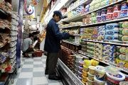 A worker checks food prices at a grocery store in Brooklyn, New York, USA, Aug. 18 2011.